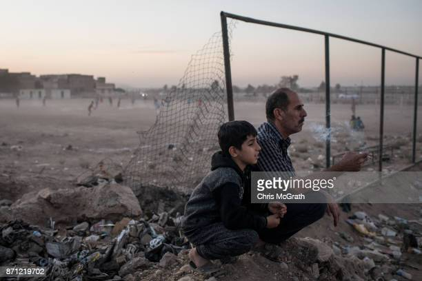 A father sits with his son to watch a local football game in East Mosul on November 5 2017 in Mosul Iraq Five months after Mosul Iraq's secondlargest...