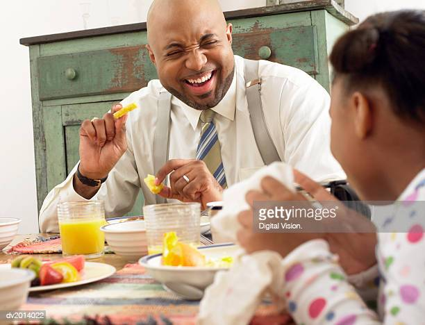 Father Sitting at the Breakfast Table Eating Fruit With His Daughter