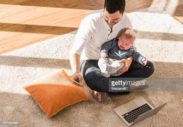Father sitting cross-legged with baby son on lap, using laptop and smart phone