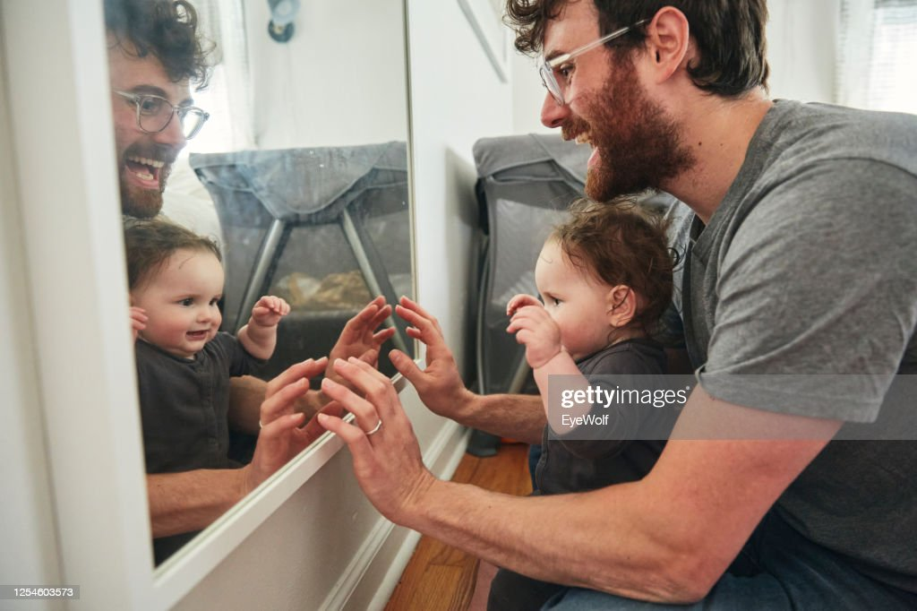 A father sitting in a bedroom with his baby daughter looking into a mirror, smiling. : Stock Photo