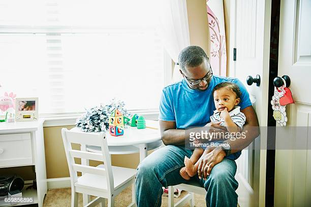 Father sitting in bedroom holding infant son