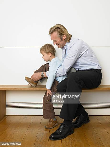 Father sitting on bench tying son's (5-7) shoelaces