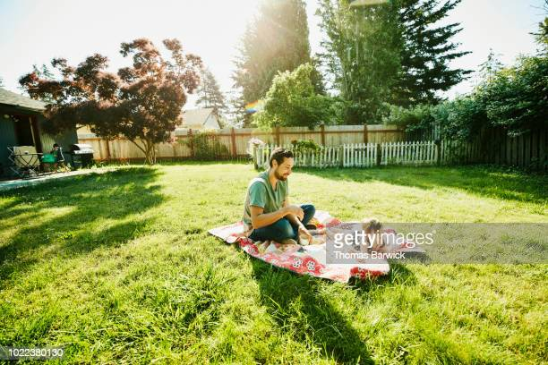 Father sitting on blanket with infant daughter in backyard on summer morning