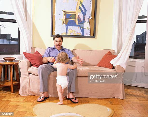Father sitting on sofa playing with daughter (18-24 months)