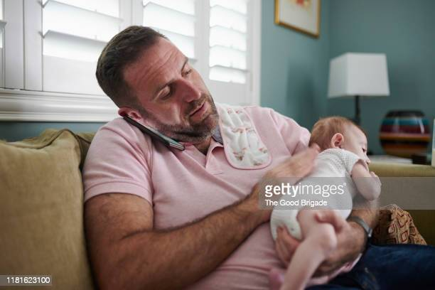 father sitting on sofa with baby while talking on mobile phone - lgbtq  and female domestic life fotografías e imágenes de stock