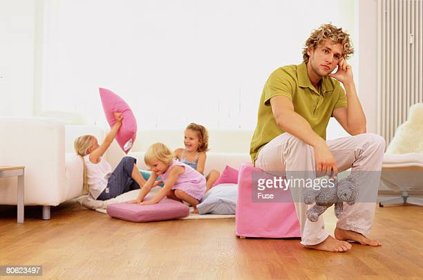 Father sitting on stool, three sisters having pillow fight