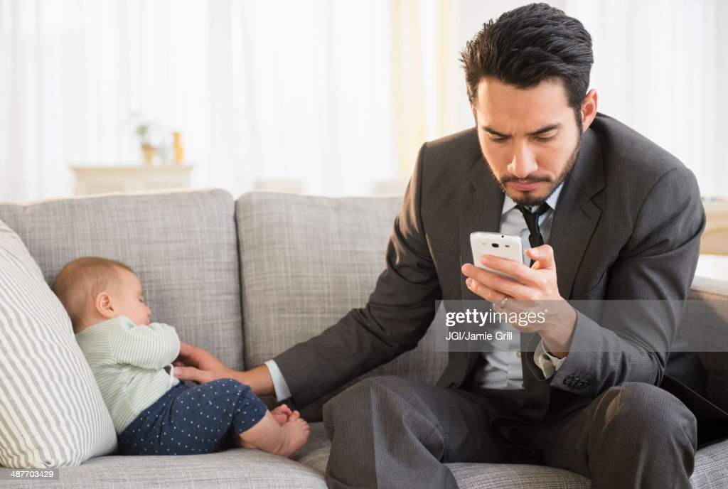 Father sitting with baby and using cell phone : Stock Photo