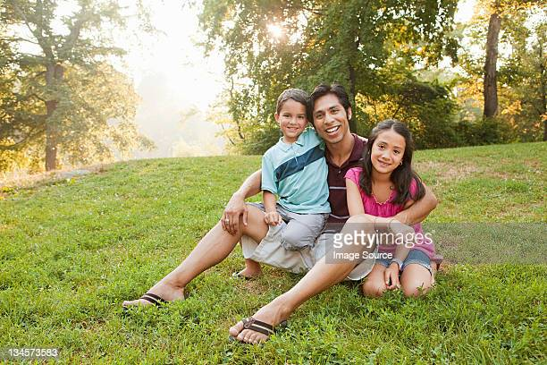 Father sitting with children in park, portrait