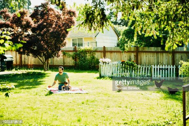 Father sitting with infant daughter on blanket in backyard