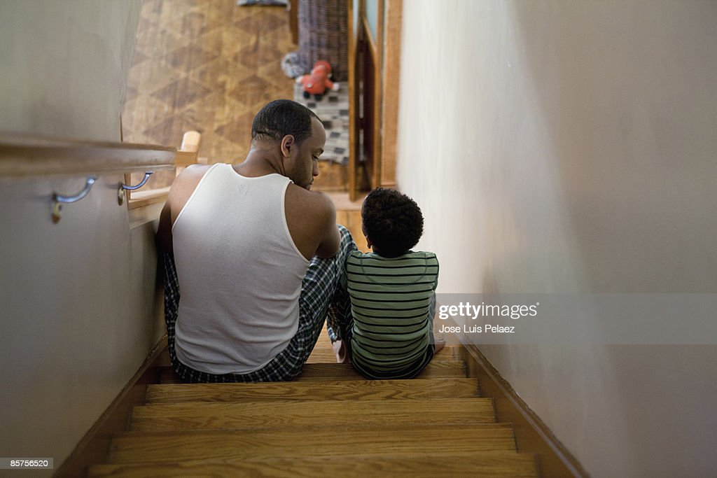 Father sitting with son on the stairs : Stock Photo