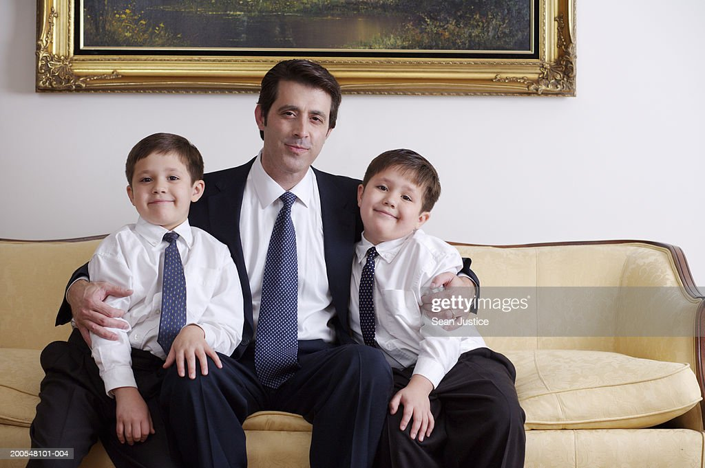 Father Sitting With Twin Sons On Sofa Smiling Portrait Stock Photo ...