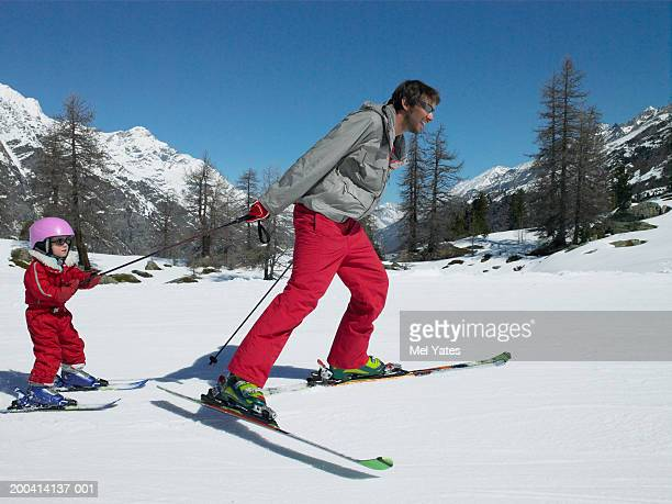 Father skiing on slope towing daughter (3-6) wearing helmet, smiling