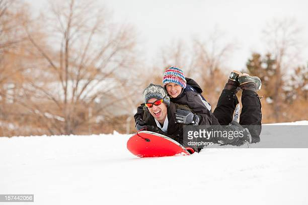 Father sledding with son riding on his back
