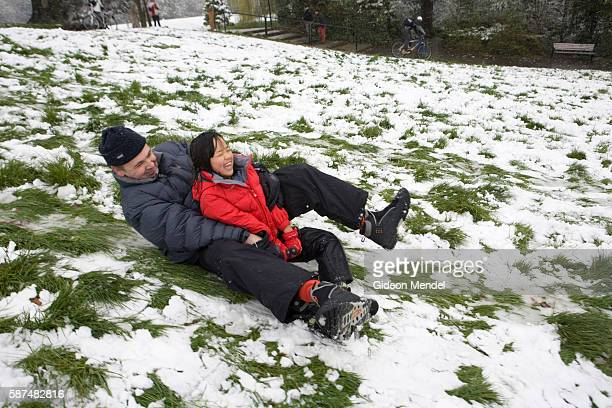 A father slides down a hill in Springfield Park on an improvised sled with his adopted Chinese daughter This was after an unseasonal snowfall in...