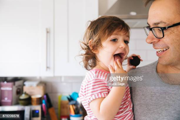 A father smiles as he holds his young girl in the kitchen
