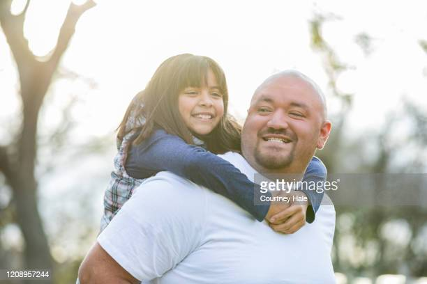 father smiles while giving piggyback ride to his elementary age daughter - mexican picnic stock pictures, royalty-free photos & images
