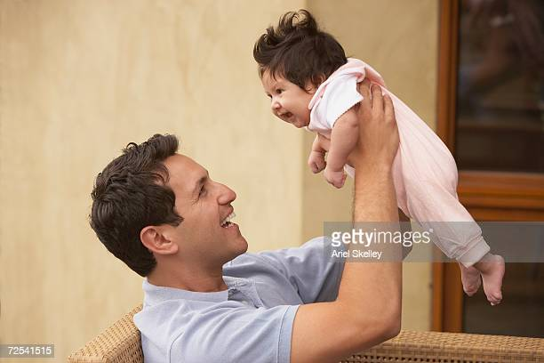 Father smiling and holding up baby