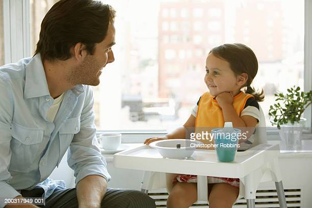 Father smiling at daughter (2-4) in high chair