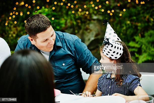 Father smiling at daughter wearing two party hats