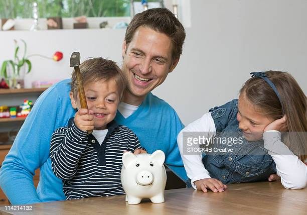 Father, son and daughter with a piggybank