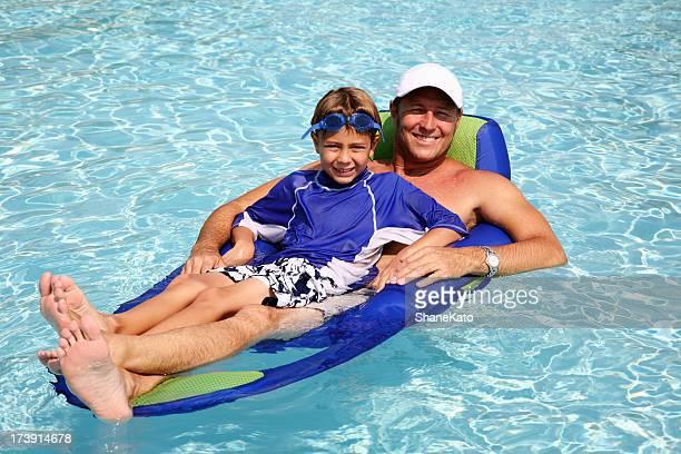 Vater und Sohn Floating auf Rafting im Schwimmbad im Sommerurlaub