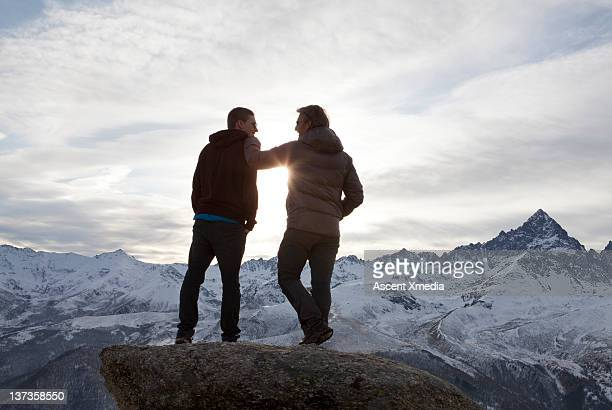 Father & son have conversation, overlooking mtns