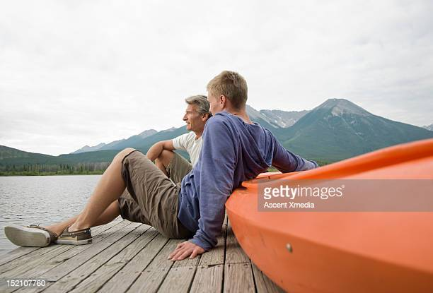 Father & son relax on dock with kayak, mtn lake