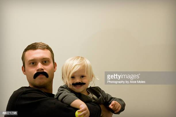 Father & Son Wearing Stick-On Moustaches
