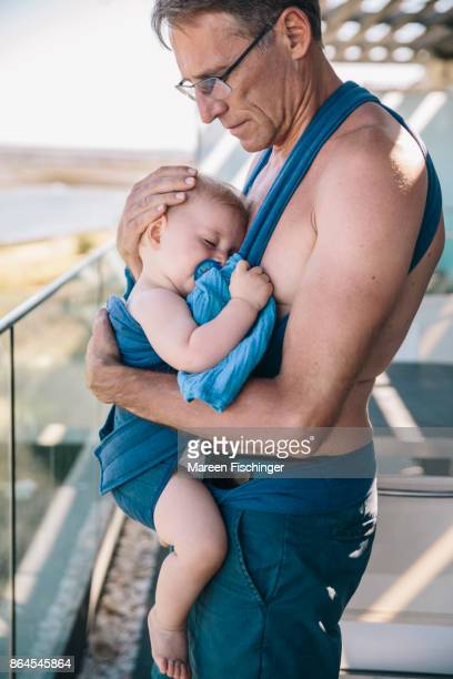 Father soothing baby in carriage skin to skin