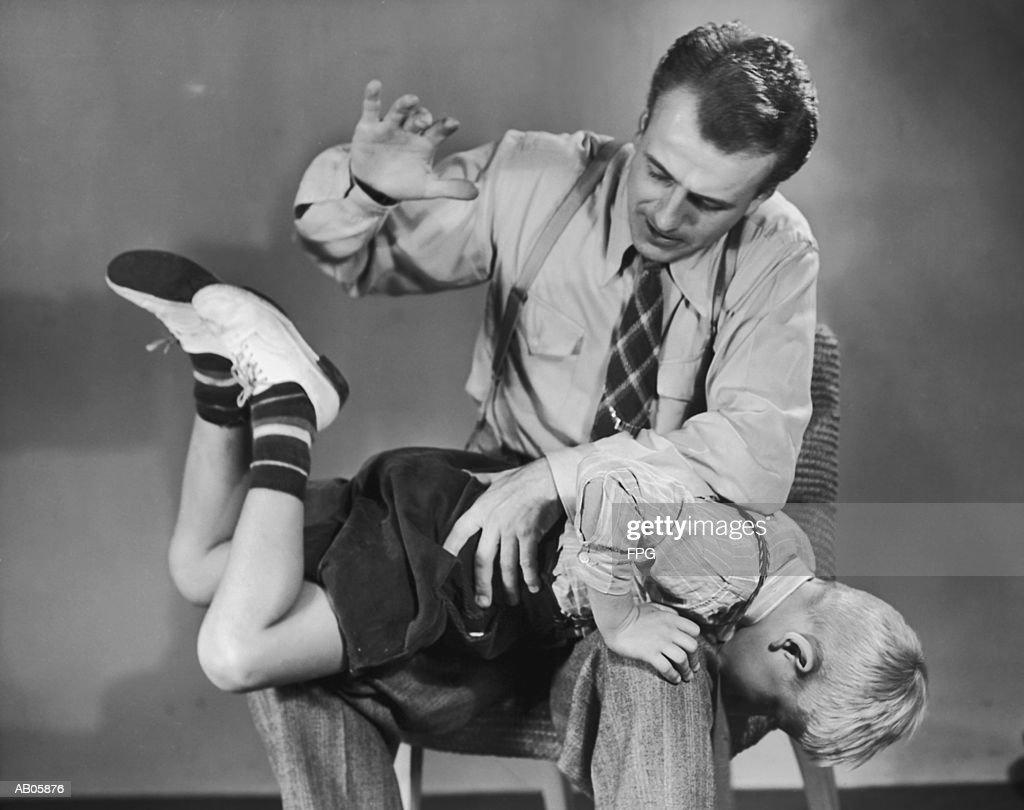 Father spanking son (5-7) on lap (B&W) : Stock Photo