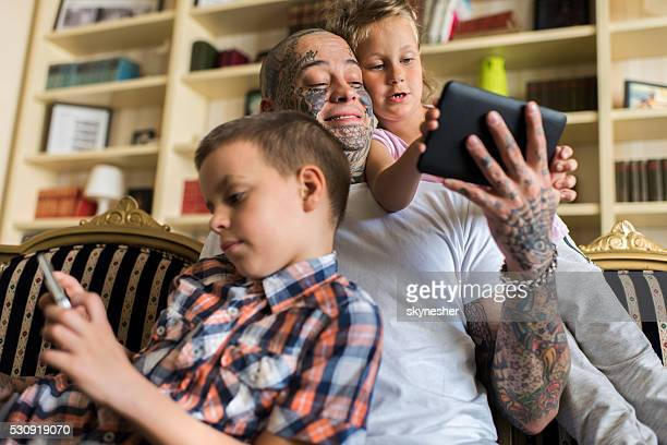 Father spending time at home with children and wireless technology.