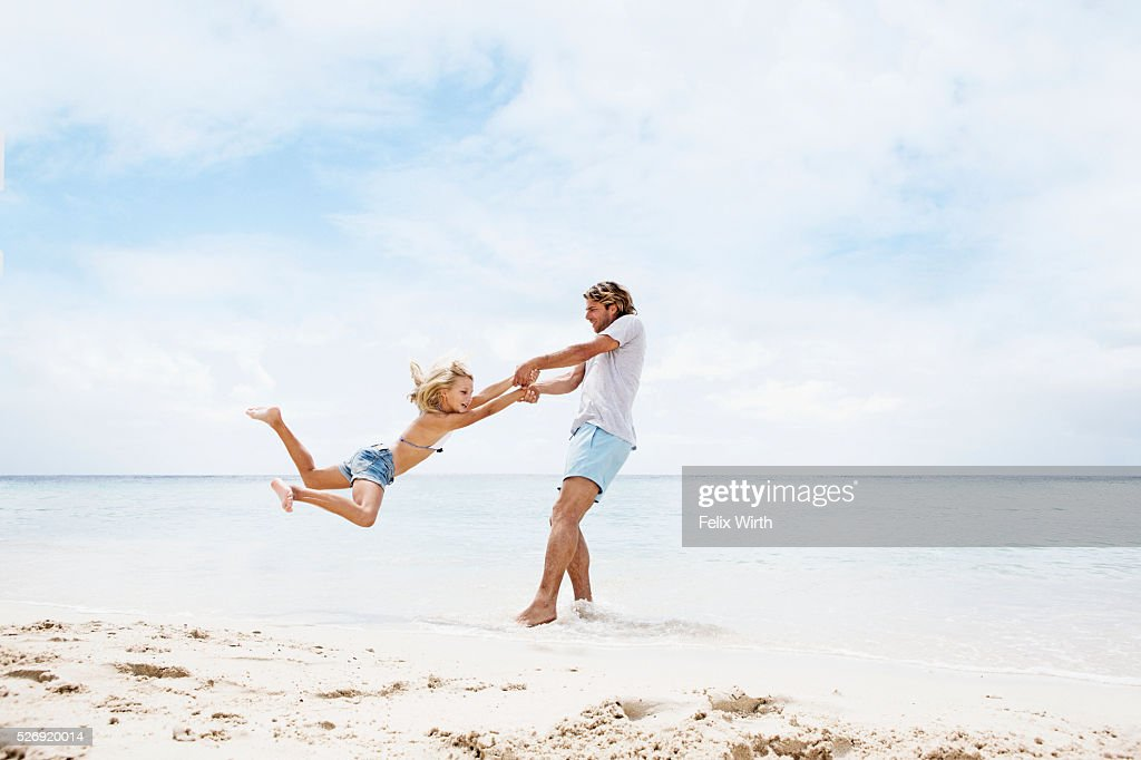 Father spinning his daughter (10-12) in air on beach : Foto stock