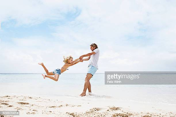Father spinning his daughter (10-12) in air on beach
