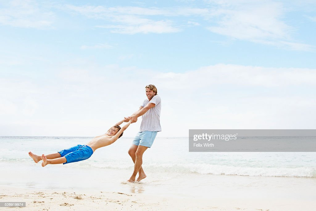 Father spinning his son (10-12) in air on beach : Stock-Foto