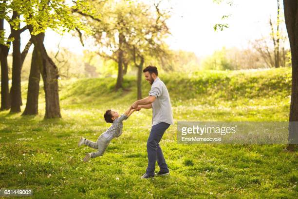 Father spinning his son in the park