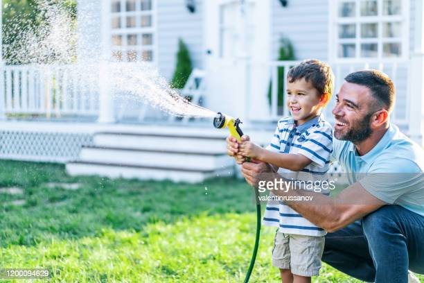 father splashing water and having fun with son on back yard - front or back yard stock pictures, royalty-free photos & images