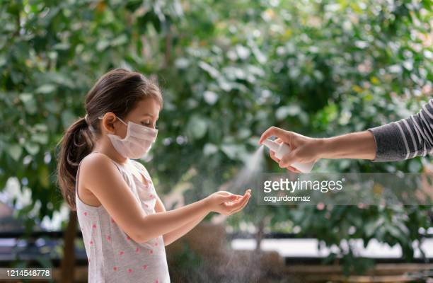 father squirts antibacterial hand sanitizer in daughter's hands, little girl wears a face mask during coronavirus and flu outbreak - alcool gel imagens e fotografias de stock