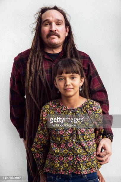 Father standing with arm around young daugher