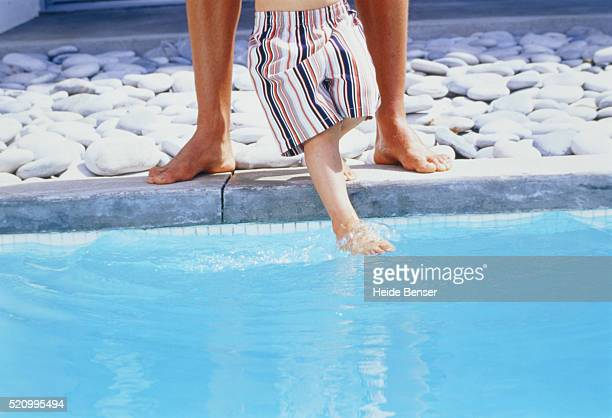 Father standing with son at swimming pool