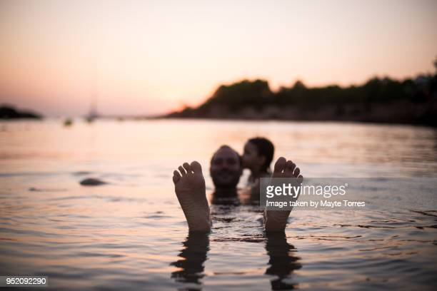 Father sticking feet out of the water while laying with son at the beach