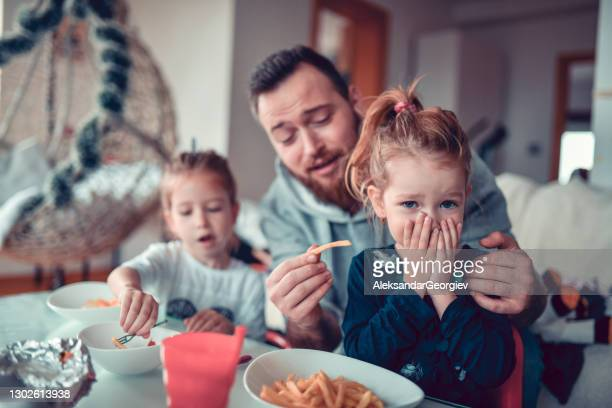 father struggling to make child daughter eat french fries - stubborn stock pictures, royalty-free photos & images