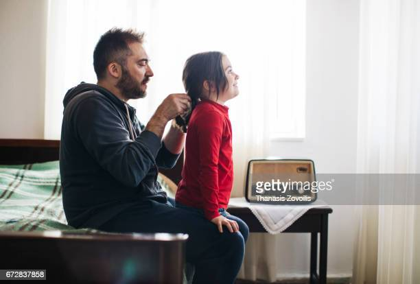 Father styling hair of his daughter at home
