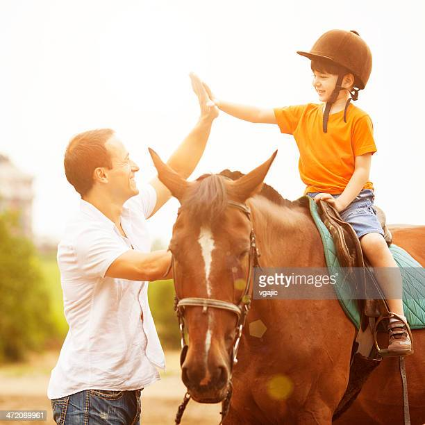 Father Support Son Riding Horse Outdoors.