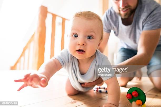 father supporting crawling baby at home - de quatro imagens e fotografias de stock