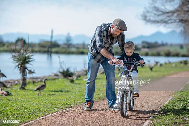 Father supporting son on bike
