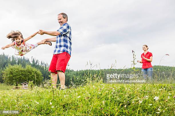 Father swinging daughter by hands and feet, Tyrol, Austria