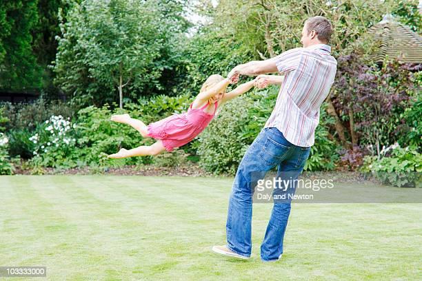 Father swinging daughter in backyard