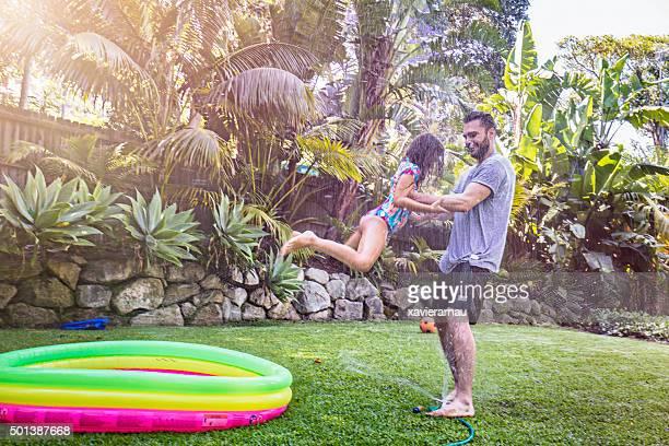 Vater schwingen Tochter im Garten