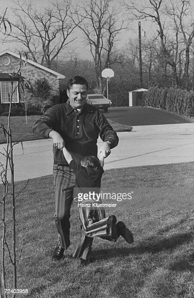 Father swinging his son playfully by the arms, on the lawn of their suburban home.