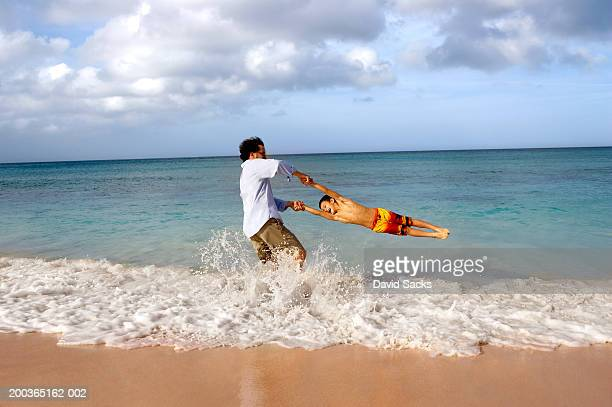 father swinging son (5-7) in ocean, side view - nassau stock pictures, royalty-free photos & images